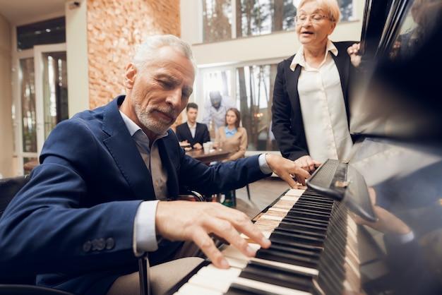 Un homme âgé joue du piano dans une maison de retraite. Photo Premium