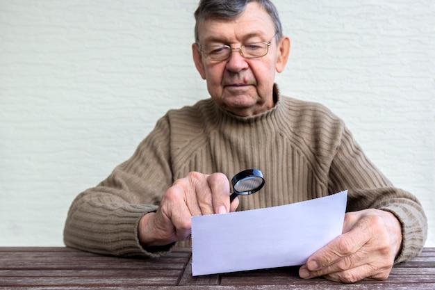 Un Homme âgé Lit Les Petits Caractères Sur Du Papier à L'aide D'une Loupe Photo Premium