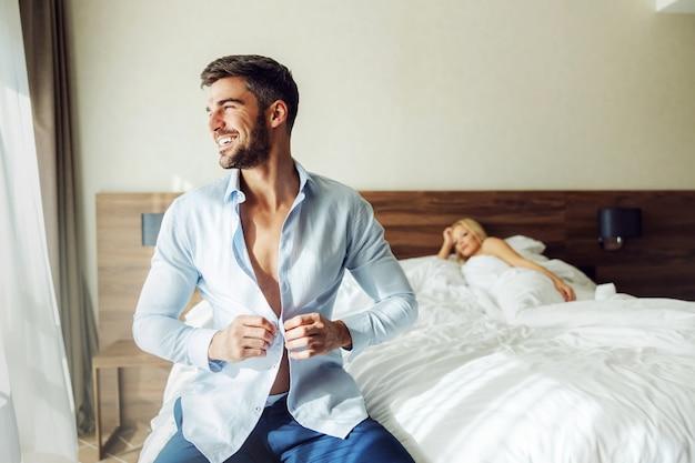 Un Homme D'âge Moyen Assis Sur Le Lit Dans Un Hôtel Et Boutonnant Sa Chemise. Photo Premium