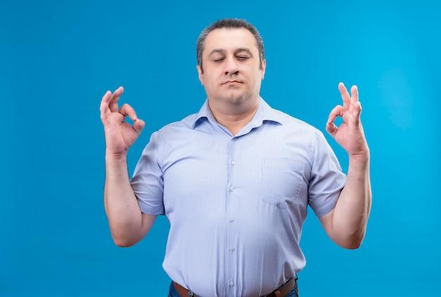 Homme D'âge Moyen Calme En Chemise Rayée Bleue Gardant Les Yeux Fermés En Faisant Un Geste Correct Avec Les Mains Sur Un Espace Bleu Photo gratuit