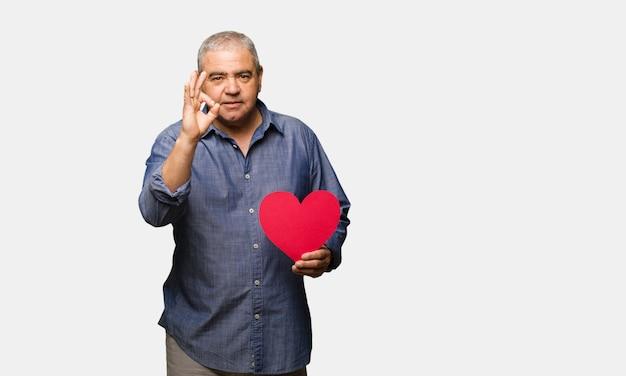 Homme âgé moyen célébrant la saint valentin gai et confiant faisant geste ok Photo Premium
