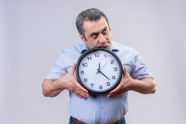 Homme D'âge Moyen En Chemise à Rayures Verticales Bleu Tenant Une Horloge Murale Dans Les Mains Réfléchie à L'idée Déroutante Sur Fond Blanc Photo gratuit