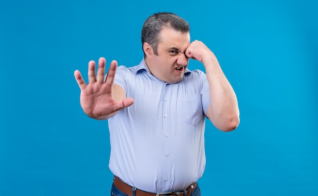 Homme D'âge Moyen En Colère Et Nerveux En Chemise Bleue Montrant Le Geste D'arrêt Avec Les Mains Sur Un Espace Bleu Photo gratuit