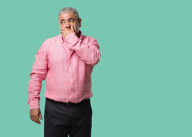 Homme d'âge moyen couvrant la bouche, symbole du silence et de la répression, essayant de ne rien dire Photo Premium
