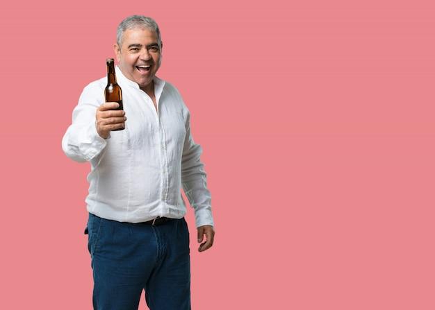 Homme d'âge moyen heureux et amusant, tenant une bouteille de bière, se sent bien après une journée de travail intense Photo Premium
