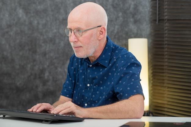 Homme d'âge mûr avec une barbe et une chemise bleue au bureau Photo Premium