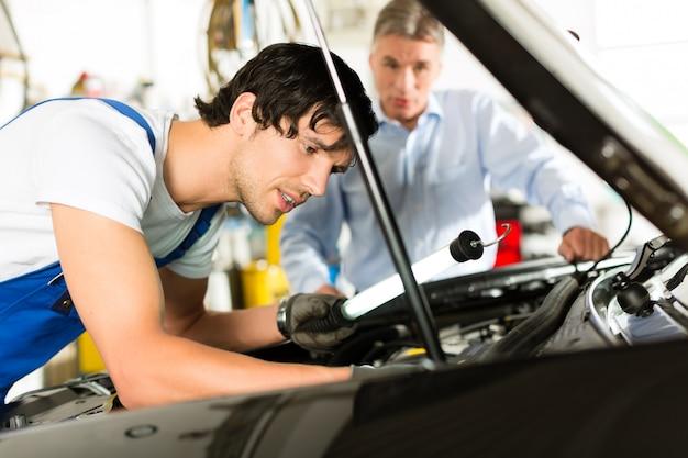 Homme d'âge mûr et mécanicien en regardant moteur de voiture Photo Premium