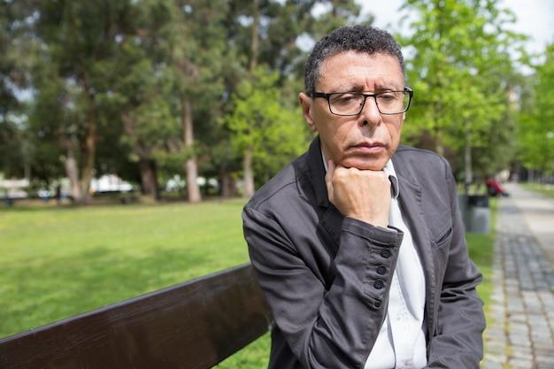 Homme d'âge mûr pensif assis sur un banc dans le parc de la ville Photo gratuit