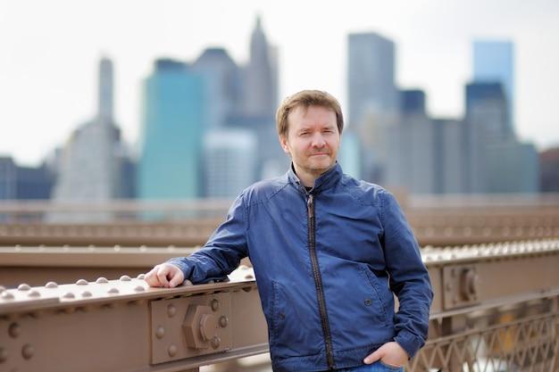 Homme d'âge mûr sur le pont de brooklyn avec des gratte-ciels sur fond Photo Premium
