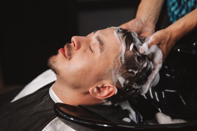 Homme d'âge mûr se faisant couper les cheveux au salon de coiffure Photo Premium