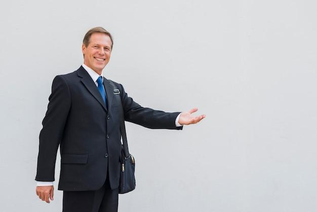 Homme d'âge mûr souriant faisant le geste de la main sur fond blanc Photo gratuit