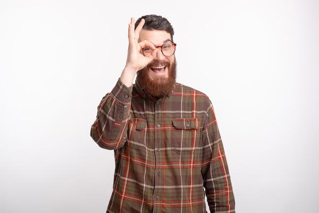 Homme D'âge Mûr Souriant Regarde à Travers Le Geste Ok Sur Fond Blanc. Photo Premium