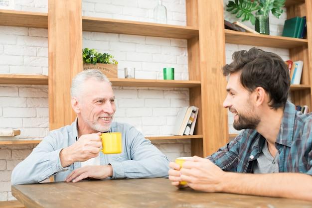 Homme âgé souriant et heureux jeune homme avec des tasses à table Photo gratuit