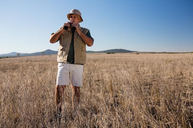 Homme à l'aide de jumelles sur le paysage Photo gratuit