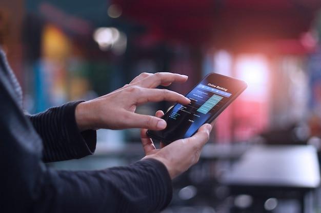 Homme à l'aide de smartphone mobile pour la banque en ligne à la cafétéria. Photo Premium