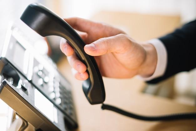 Homme à l'aide de téléphone au bureau Photo gratuit