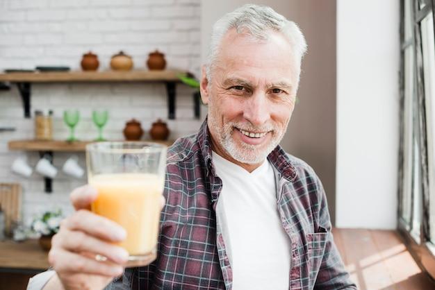Homme aîné ayant un jus Photo gratuit