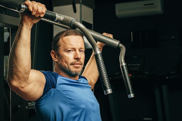 Homme Aîné, Faire, Exercices Bras, Dans, A, Machine Entraînement, Dans, Gymnase Photo Premium