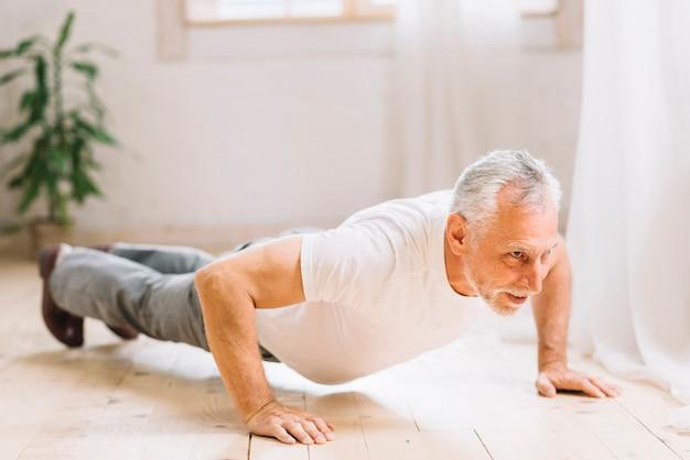 Homme aîné, faire, pushup, exercice, sur, plancher bois franc Photo gratuit