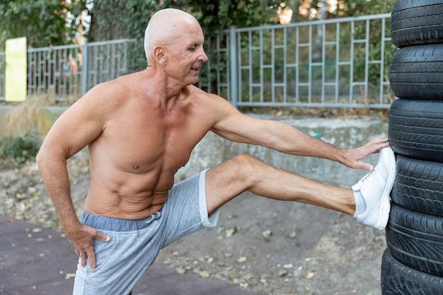 Homme Aîné Musclé Qui S'étend à L'extérieur Photo gratuit