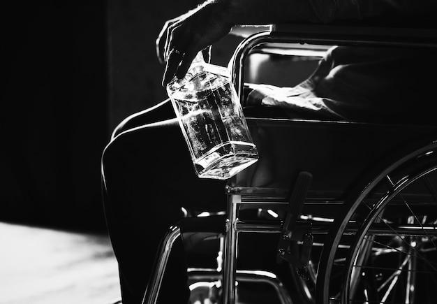 Homme alcoolique assis dans un fauteuil roulant Photo gratuit