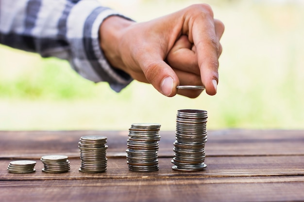 Homme alignant des pièces de monnaie sur le concept d'échelle Photo gratuit