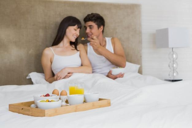 Homme, alimentation, céréales petit déjeuner, à, femme, dans, chambre à coucher Photo Premium
