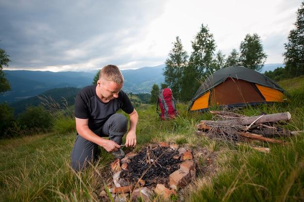 Homme allumant du bois de chauffage sur la colline Photo Premium
