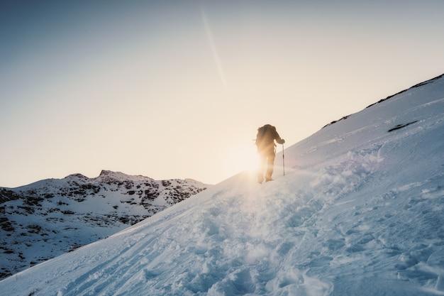 Homme alpiniste escalade à la montagne en hiver au coucher du soleil Photo Premium