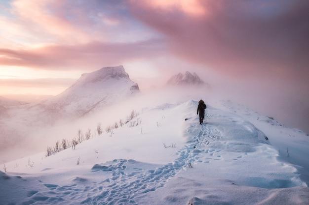 Homme alpiniste marchant avec empreinte de neige sur la crête de neige en blizzard Photo Premium