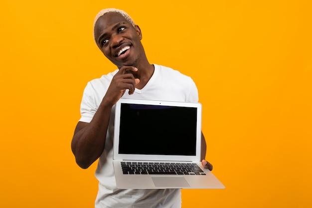 Homme Américain Souriant Joyeux Attrayant Tenant Un Ordinateur Portable Avec Une Maquette Et Rêvant Sur Fond Jaune Photo Premium