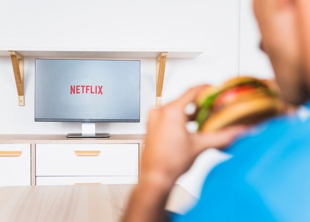 Homme anonyme avec hamburger regardant la série tv Photo gratuit