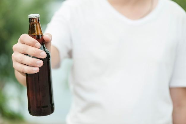 Homme anonyme montrant une bouteille de bière Photo gratuit