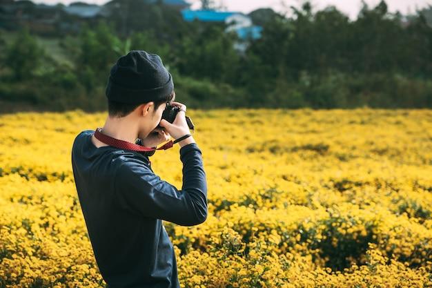 Homme Avec Un Appareil Photo à Prendre Des Photos De Fleurs Photo Premium