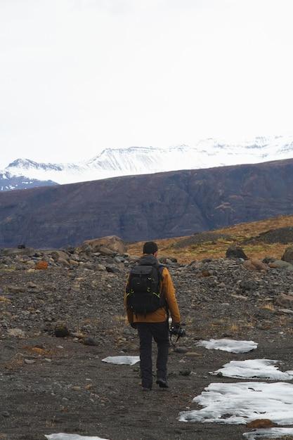 Homme Avec Un Appareil Photo Randonnée Entouré De Montagnes Rocheuses Couvertes De Neige En Islande Photo gratuit