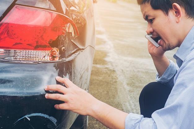 Un homme appelle une compagnie d'assurance pour avoir revendiqué l'accident de sa voiture endommagé lors d'un accident de la route Photo gratuit