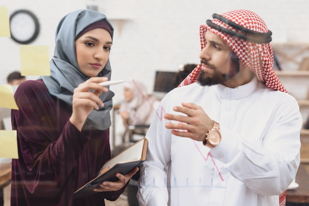 Homme arabe et femme d'affaires créent un diagramme. Photo Premium
