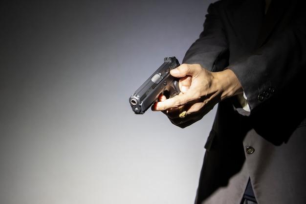 Homme armé tenant arme à feu avec fond sombre Photo Premium
