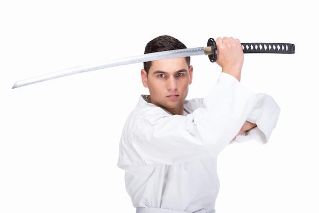 Un homme d'arts martiaux est debout avec une épée. Photo Premium