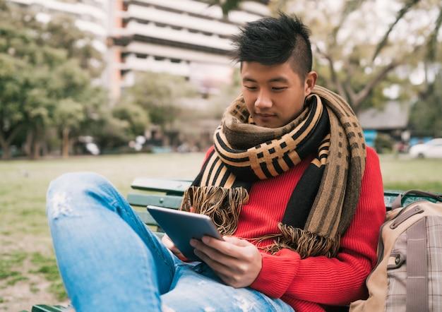 Homme Asiatique à L'aide De Sa Tablette Numérique. Photo gratuit