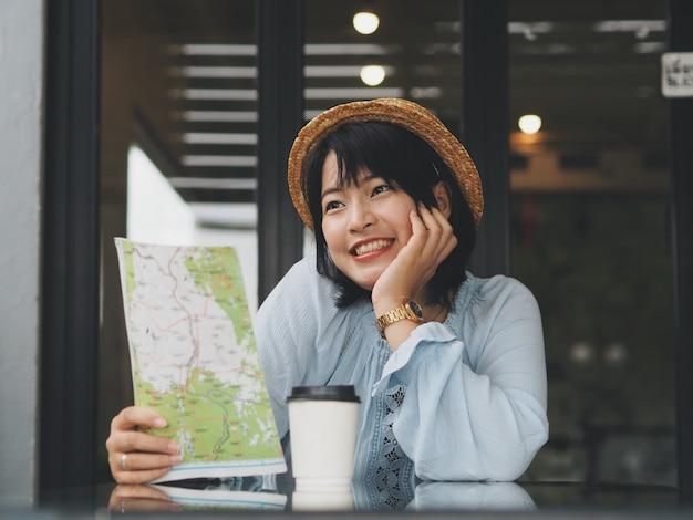 Homme asiatique attrayant tenant la carte et de boire du café au café. Photo Premium