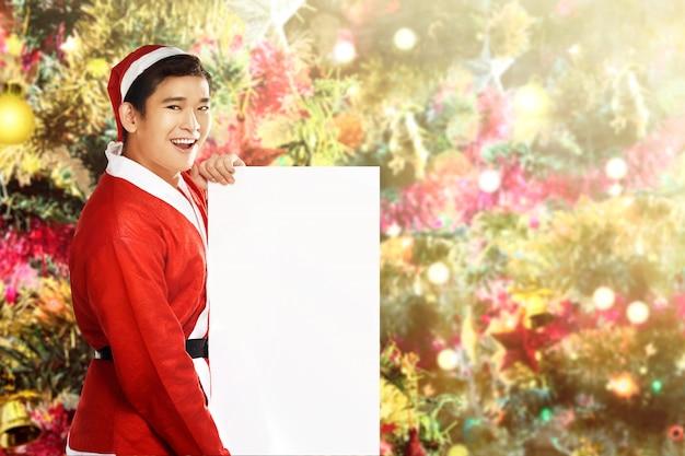 Homme asiatique en costume de père noël tenant un tableau blanc avec un sapin de noël décoré Photo Premium