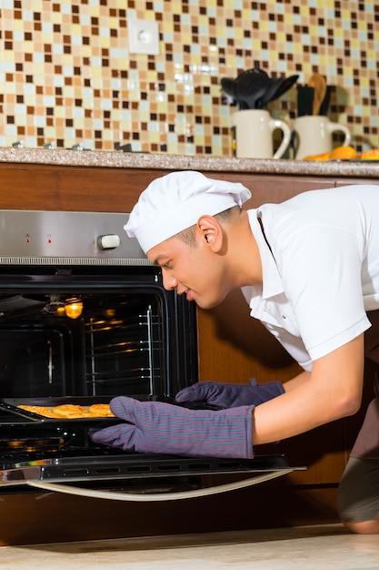 Homme asiatique, cuisson, gâteau, dans, cuisine maison Photo Premium