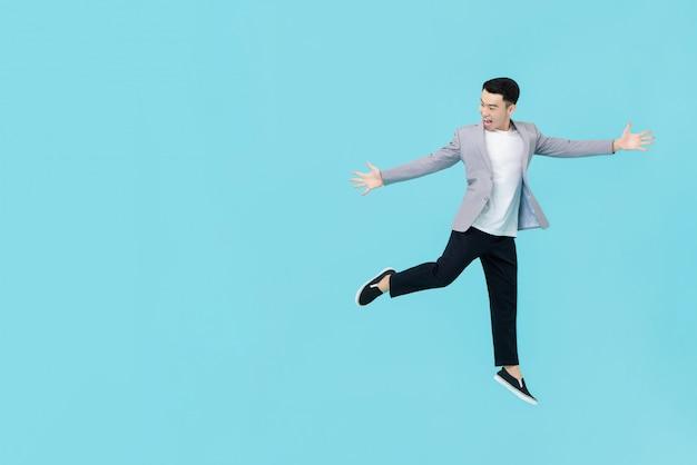 Homme Asiatique Dans Des Vêtements Décontractés Intelligents, Tendant Les Mains Et Sautant Avec Enthousiasme Photo Premium