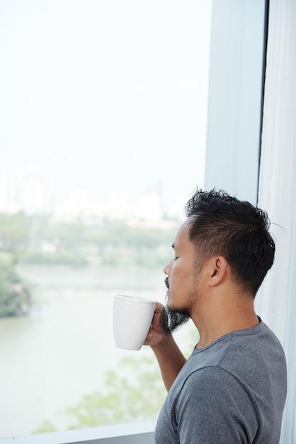 Homme Asiatique, Debout, Devant, Fenêtre, Et, Sentant, Tasse Café, à, Yeux Fermés Photo gratuit