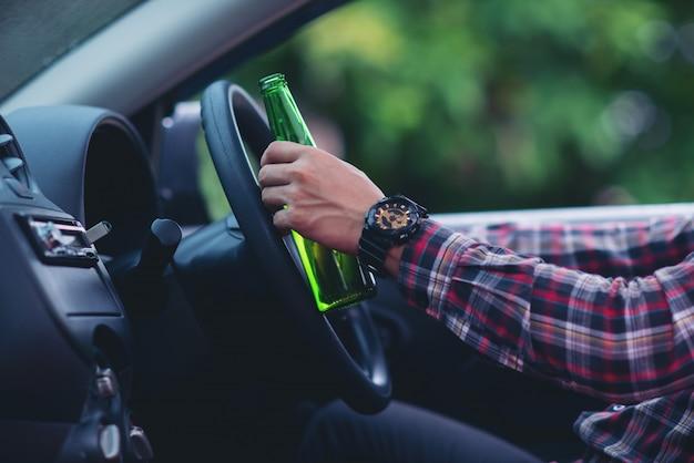 Homme asiatique détient une bouteille de bière tout en conduisant une voiture Photo gratuit