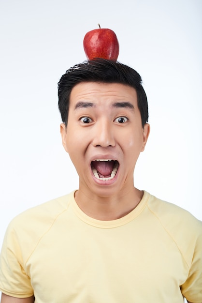 Homme asiatique effrayé avec pomme rouge Photo gratuit