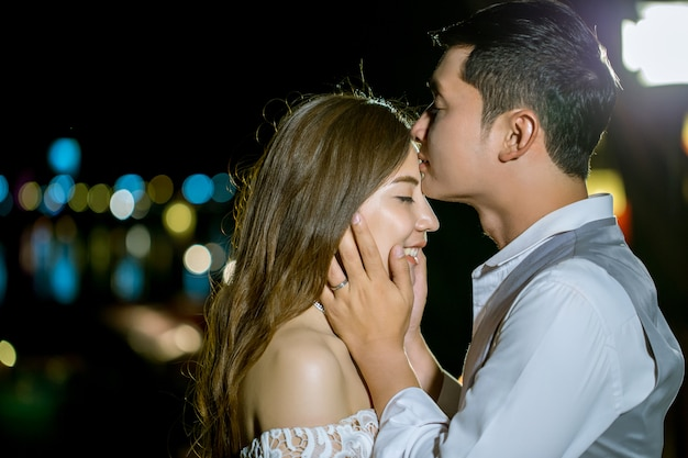 Homme asiatique embrassant la tête de sa petite amie. au doux soir. Photo Premium