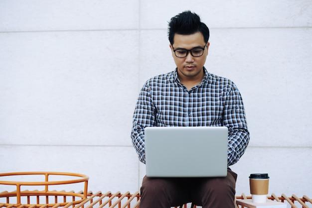 Homme Asiatique à Lunettes, Assis Sur Un Banc à L'extérieur Et Travaillant Sur Un Ordinateur Portable Photo gratuit