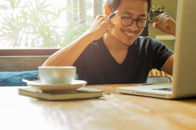 Un homme asiatique avec un ordinateur portable a levé la main pour célébrer le succès de bonnes nouvelles. Photo Premium